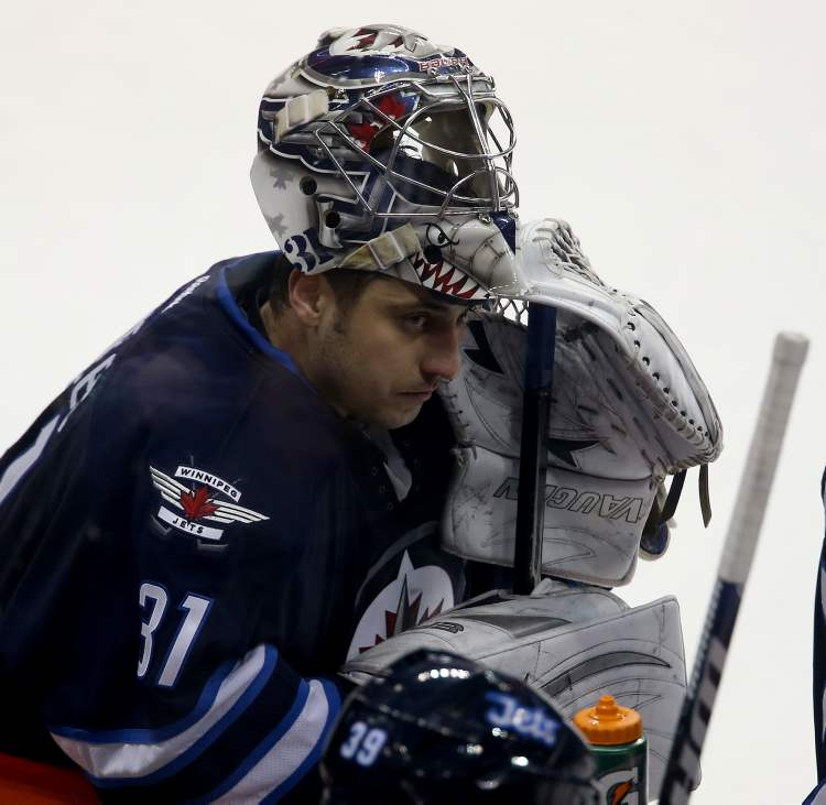 Winnipeg Jets' goaltender Ondrej Pavelec (31) rests at the bench during a break in third-period action.