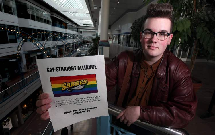 "Evan Wiens holds up the poster he will now be allowed to distribute promoting the ""Sabres"" Gay Straight Alliance in Steinbach."