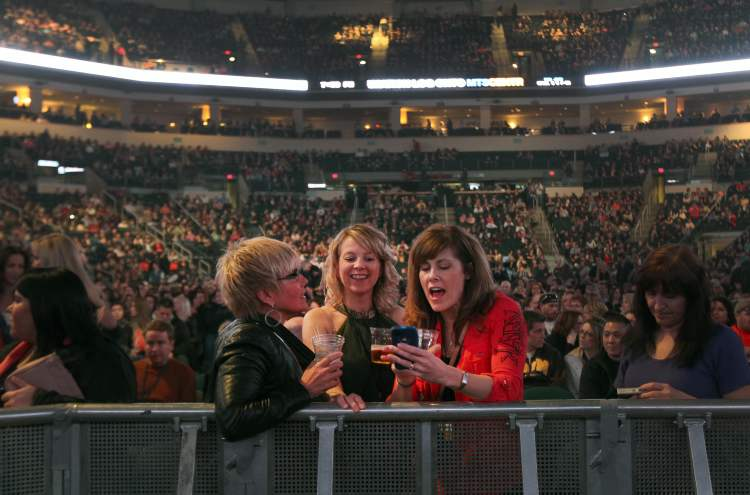 Female spectators have some fun before Bon Jovi hits the stage.