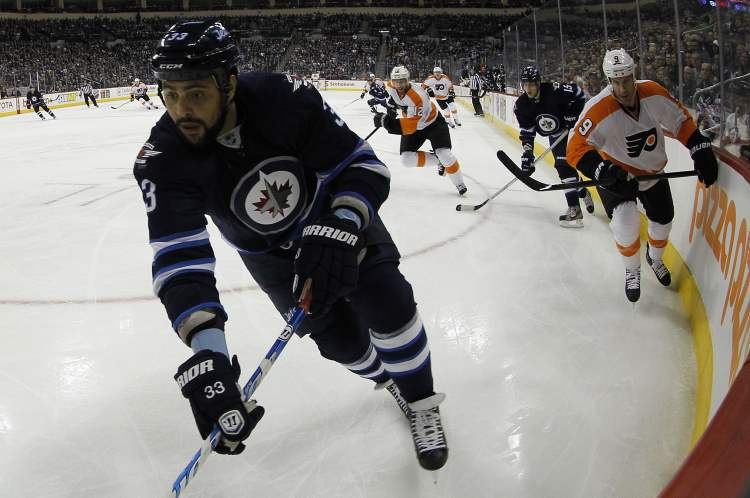 Winnipeg Jets' Dustin Byfuglien (33) reaches for the puck as he is pursued by Philadelphia Flyers forward Mike Knuble (9) at the MTS Centre Saturday. (TREVOR HAGAN / WINNIPEG FREE PRESS)
