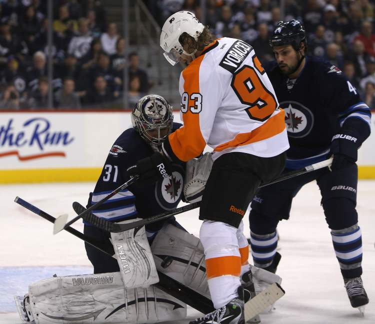 Winnipeg Jets' goaltender Ondrej Pavelec (31) saves the puck with Philadelphia Flyers Jakub Voracek (93) on the doorstep during the first period of Saturday afternoon's game. (TREVOR HAGAN / WINNIPEG FREE PRESS)