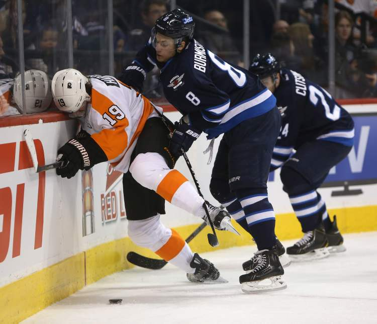 Winnipeg Jets' Alexander Burmistrov (8) shoves Philadelphia Flyers' Scott Hartnell (19) into the boards during the first period of Saturday afternoon's game.