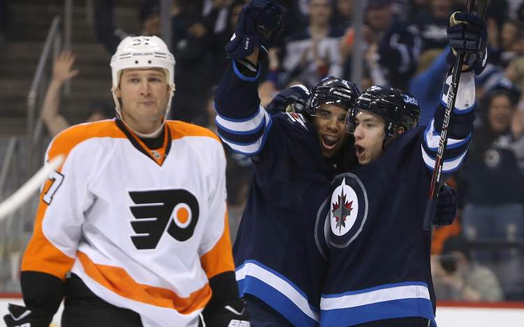 Winnipeg Jets' Evander Kane (9) and Alexander Burmistrov (8) celebrate after Kane scored during the second period as Philadelphia Flyers' Jay Rosehill (37) looks on.