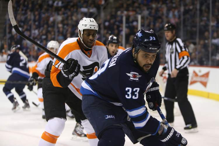 Winnipeg Jets' Dustin Byfuglien (33) is chased into the corner by Philadelphia Flyers' Wayne Simmonds (17) during the second period NHL hockey action, Saturday. The Jets returned from a poor first period and defeated the Flyers 4-1. (TREVOR HAGAN / WINNIPEG FREE PRESS)