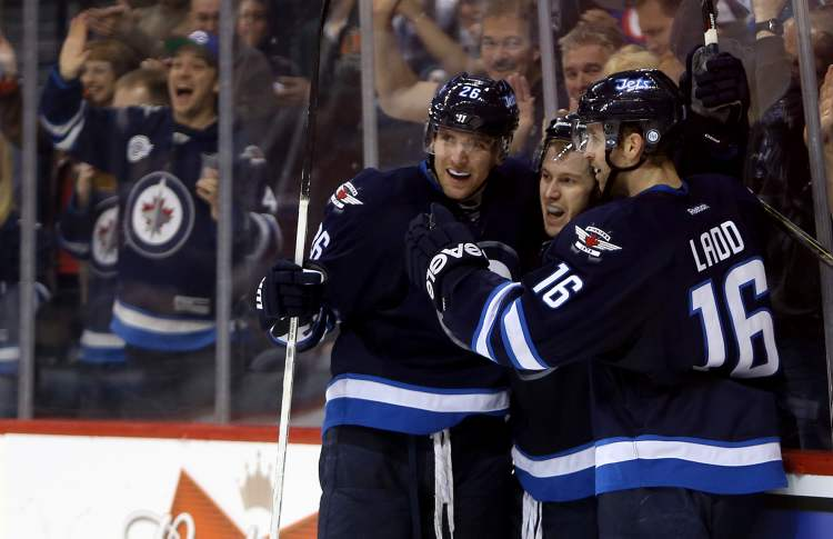 Winnipeg Jets' Blake Wheeler (26), Bryan Little (18) and Andrew Ladd (16) celebrate after Little scored during the second period against the Philadelphia Flyers Saturday afternoon. The Jets ended a five-game losing streak, beating the Flyers 4-1.