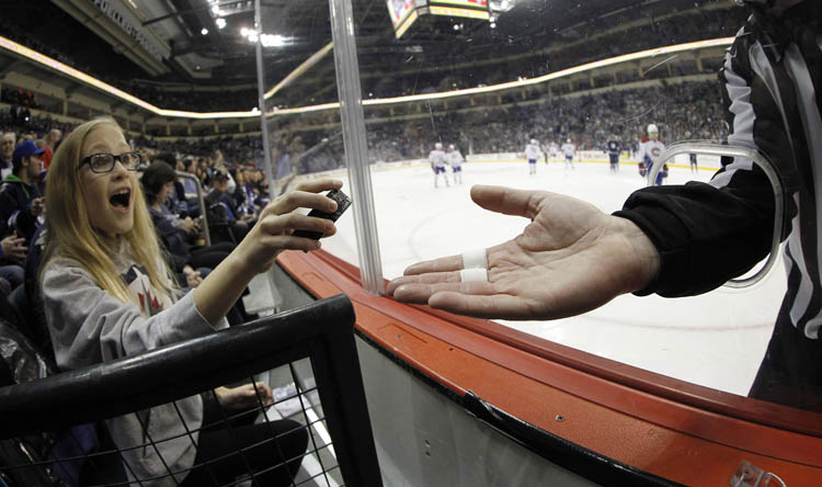 Linesman Brad Kovachik hands a game puck to Theresa Buchel, 10, during the first period of the Montreal Canadiens versus Winnipeg Jets game at MTS Centre on Thursday. (TREVOR HAGAN/WINNIPEG FREE PRESS)
