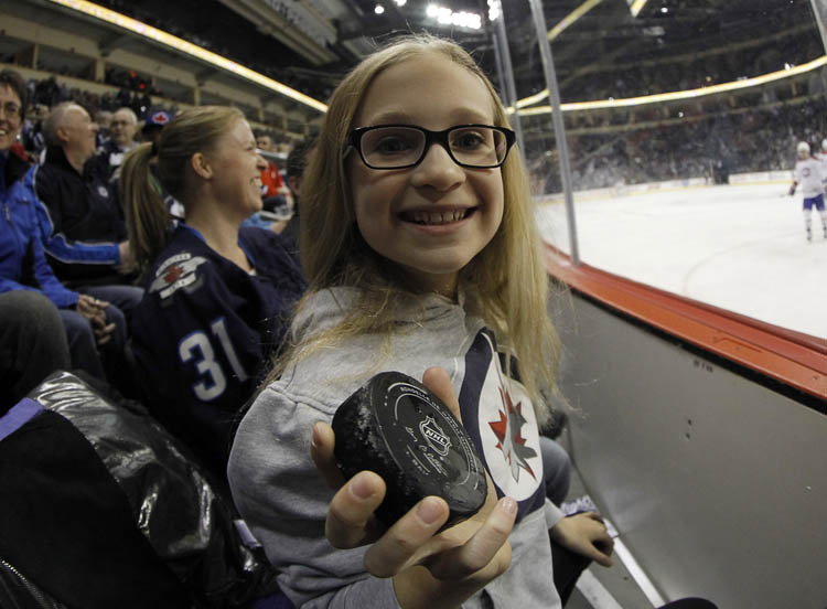 Theresa Buchel, 10, holds the game puck she was handed by linesman during the first period of the Montreal Canadiens against Winnipeg Jets Thursday night.