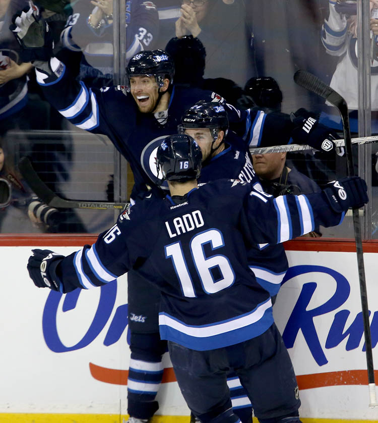 Winnipeg Jets' Blake Wheeler (26), Grant Clitsome (24) and Andrew Ladd (16) celebrate after Wheeler scored to retake the lead against the Montreal Canadiens' in the second period. (TREVOR HAGAN / WINNIPEG FREE PRESS)