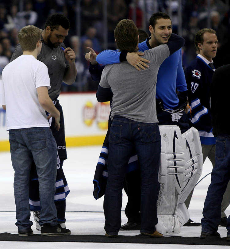 Dustin Byfuglien signs his jersey and Ondrej Pavelec gives a hug to a pair of lucky winners of the players jerseys after the Winnipeg Jets' final home game of the season versus the Montreal Canadiens on Thursday. (Trevor Hagan / Winnipeg Free Press)