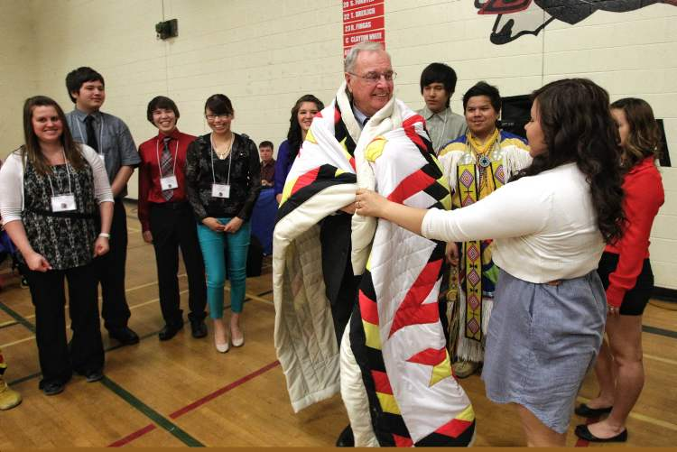 Students in the Martin Aboriginal Education Initiative present a star blanket to former prime minister  Paul Martin during a school assembly at Major Pratt School in Russell Wednesday.