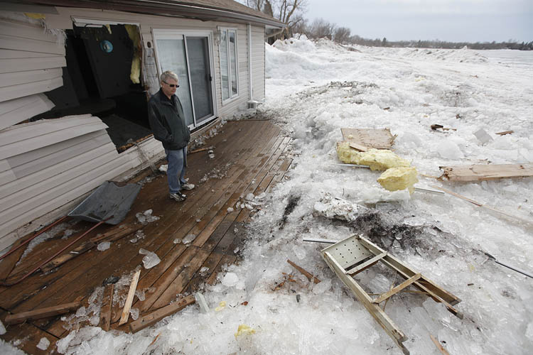 After clearing snow piled to the roof with his sons, Lorne Perche stands amid the destruction of his cottage on Ochre Beach lake ice was blown ashore by strong winds two days earlier on Friday, May 10, 2013. (John Woods / Winnipeg Free Press)
