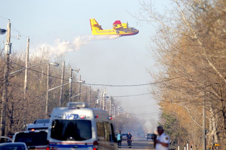 One of two water bombers flies over the area to help extinguish the flames. (BORIS MINKEVICH / WINNIPEG FREE PRESS)
