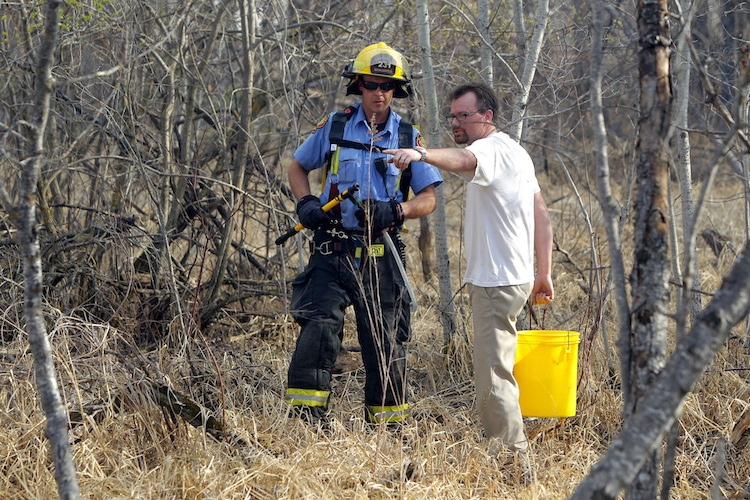 A resident from the area and firefighter survey the grass fire.