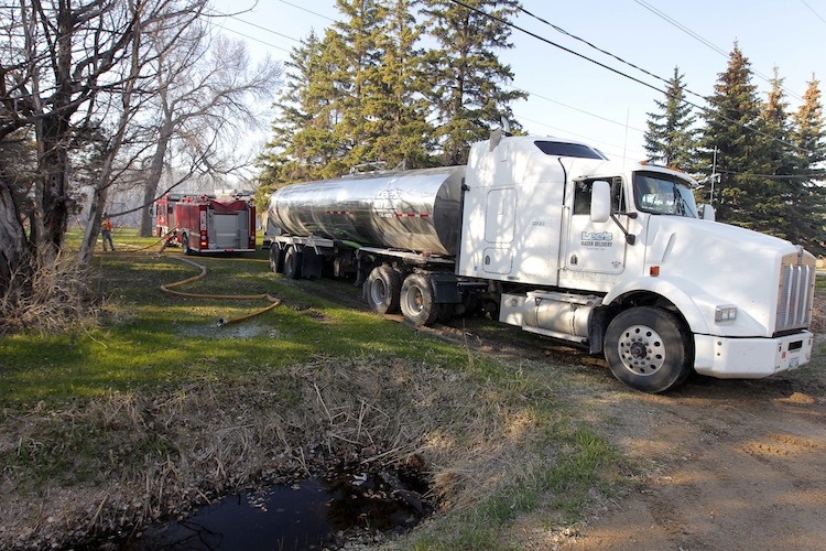 A water tanker and fire truck are lined up near the Fraser Road grass fire. (BORIS MINKEVICH / WINNIPEG FREE PRESS)
