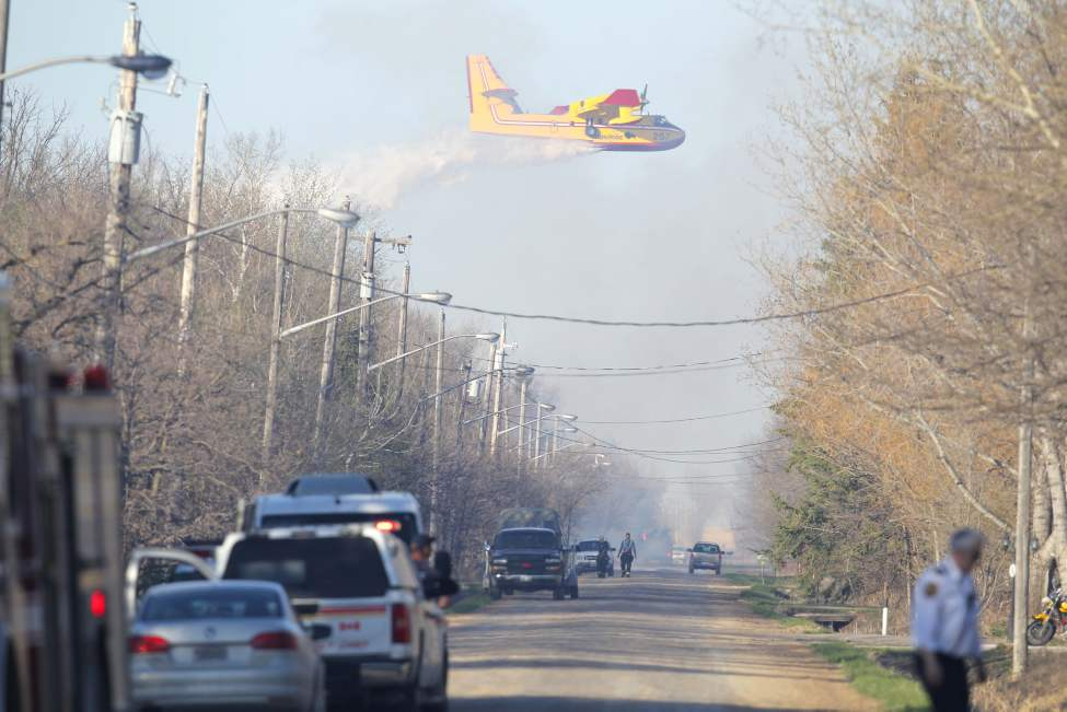 A water bomber flies over a grass fire burning near Fraser Road in south Winnipeg Wednesday evening. May 15, 2013  BORIS MINKEVICH / WINNIPEG FREE PRESS (Boris Minkevich)