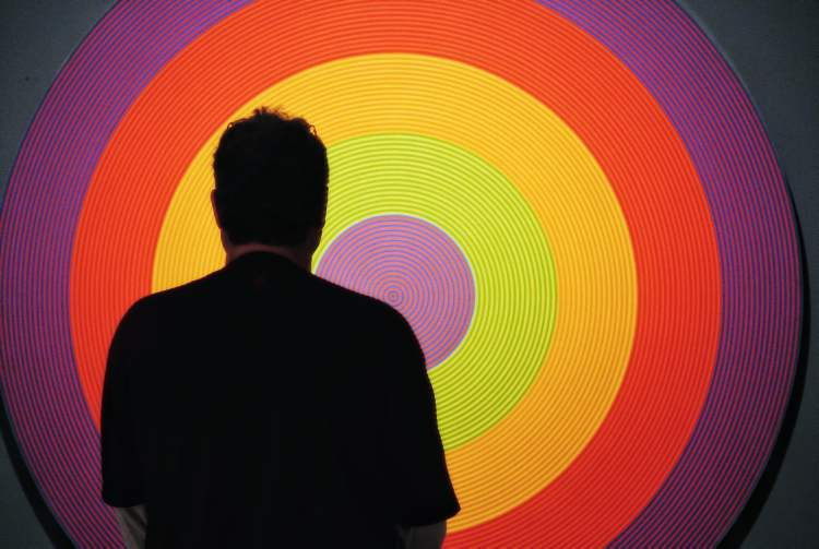 A visitor to the gallery listens to an audio tour while looking at Claude Tousignant's Gong 80, 1966.