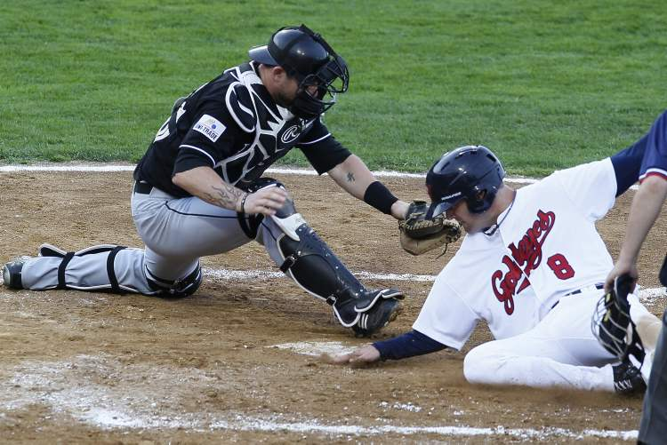 Nick Liles (8) of the Winnipeg Goldeyes beats the tag at home from Brian Peterson (26) of the Laredo Lemurs.
