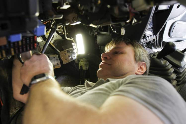 Immobilizer installer Ray McKee puts one of the anti-theft devices on an SUV.