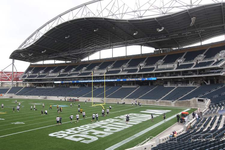 Players practising at Investors Group Field Monday. There will be 5,000 paid parking spots on the campus for seasonal passes.