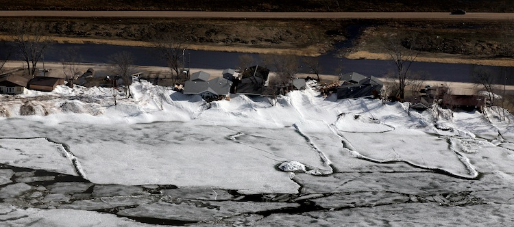 The sun shines on Ochre Beach as piles of ice are seen pressed up against homes. (Phil Hossack / Winnipeg Free Press)