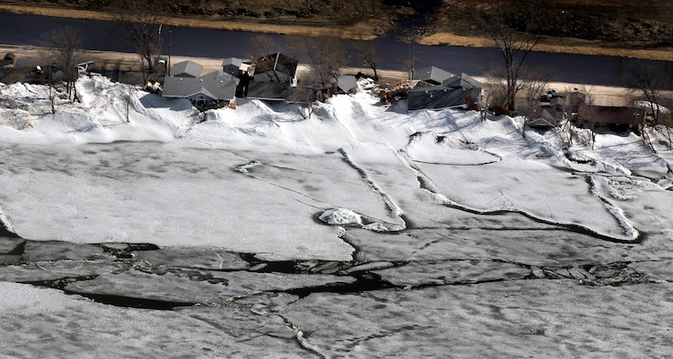 Ice has started breaking up on Dauphin Lake, with larger piles along the shoreline pressed up against houses.  (Phil Hossack / Winnipeg Free Press)