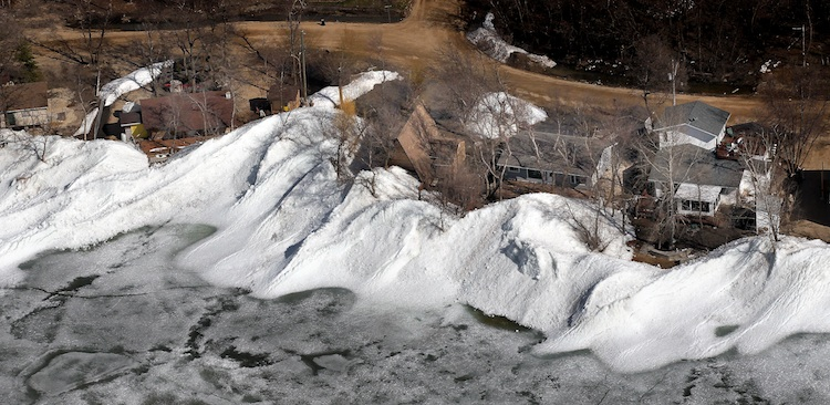 Piles of ice are pushed up against a row of homes. (Phil Hossack / Winnipeg Free Press)
