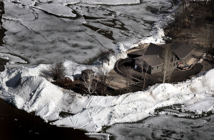 Piles of ice surround a property in Ochre Beach. (Phil Hossack / Winnipeg Free Press)