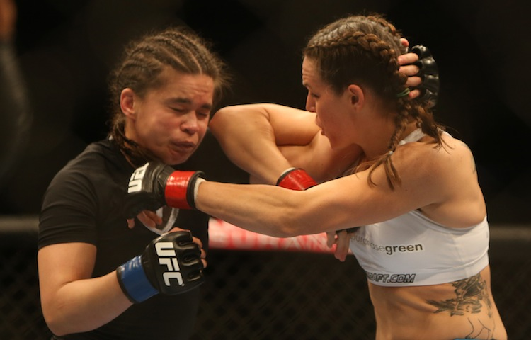 Alex Davis (right) hits Rosi Sexton with an elbow during their bantamweight bout. (TREVOR HAGAN / WINNIPEG FREE PRESS)