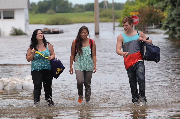Daveena Zorn (left), Natasha Morrison and Garrett Adcock walk along a flooded street in the community of Reston after Adcock's vehicle stalled on a flooded road outside of town Wednesday. The trio were headed home from Zorn's grad ceremonies, which was the previous day, and had to walk to Reston when their vehicle became flooded. (Tim Smith / Brandon Sun)