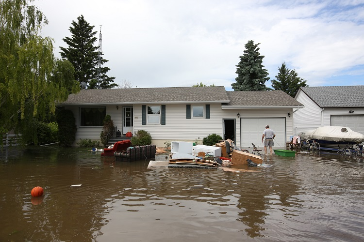 Furniture and appliances sit in flood water surrounding a home in the community of Reston Wednesday. Another powerful storm flooded several streets in the community Tuesday, causing more flooding. (Tim Smith / Brandon Sun)