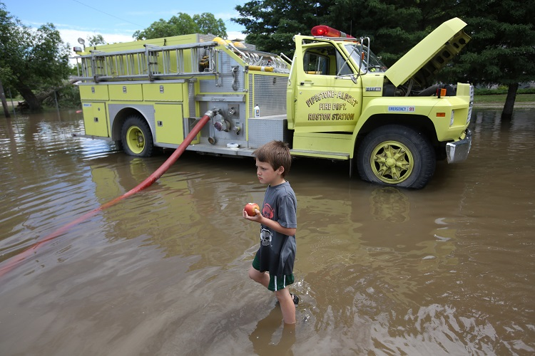 Six-year-old Aiden Sanderson eats an apple while exploring the flood water on 2nd Street in the community of Reston on Wednesday. Several families whose homes were flooded over the weekend were in the midst of cleaning up when Tuesday evenings storm caused flooding again.