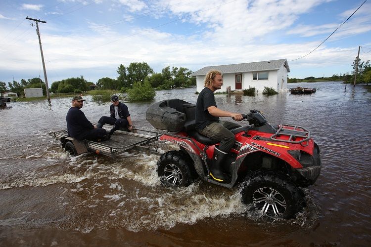 Men drive a quad along a flooded street in the community of Reston while helping in the flood relief efforts Wednesday. (Tim Smith / Brandon Sun)