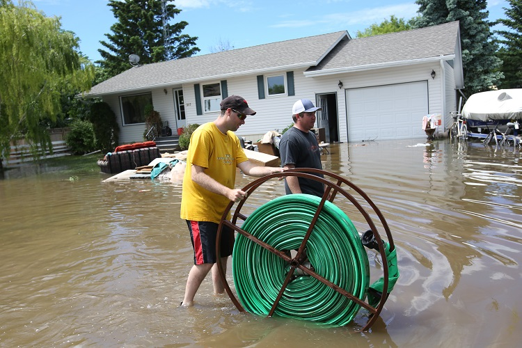 Vince Moore (left) and Chris Flannery help set up pumps to in the community of Reston Wednesday. Their homes were high and dry, so they volunteered to help those who weren't so fortunate. (Tim Smith / Brandon Sun)