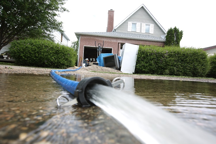 Water is pumped out of the basement of a Reston home. (Tim Smith / Brandon Sun)