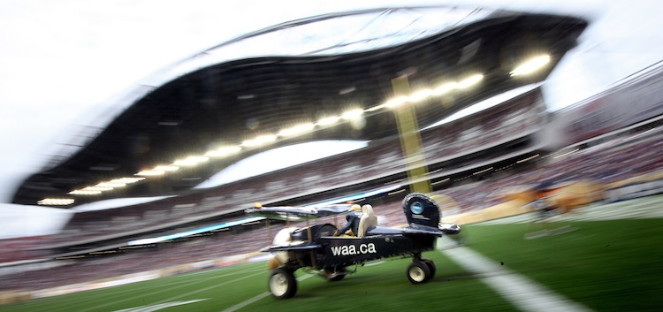 A miniature airplane buzzes on the turf before kickoff at Investors Group Field.
