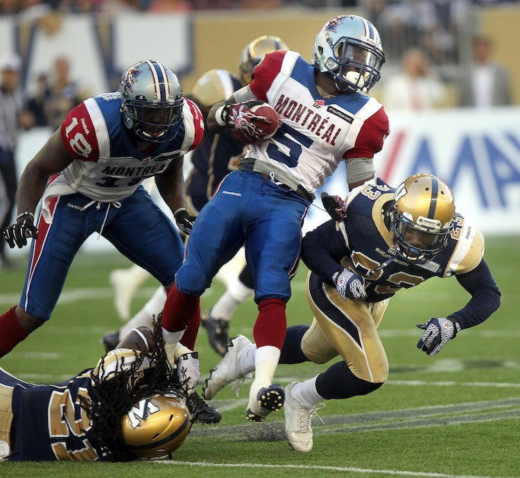 Montreal's Noel Devine (5) sails through Alex Suber (21) and Desia Dunn (23) of the Bombers Thursday. (Phil Hossack / Winnipeg Free Press)