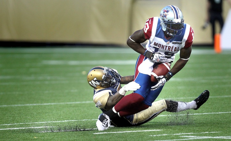 Montreal Alouettes' S.J. Green (19) is taken down by Winnipeg Blue Bomber Demond Washington in the second quarter. (Phil Hossack / Winnipeg Free Press)