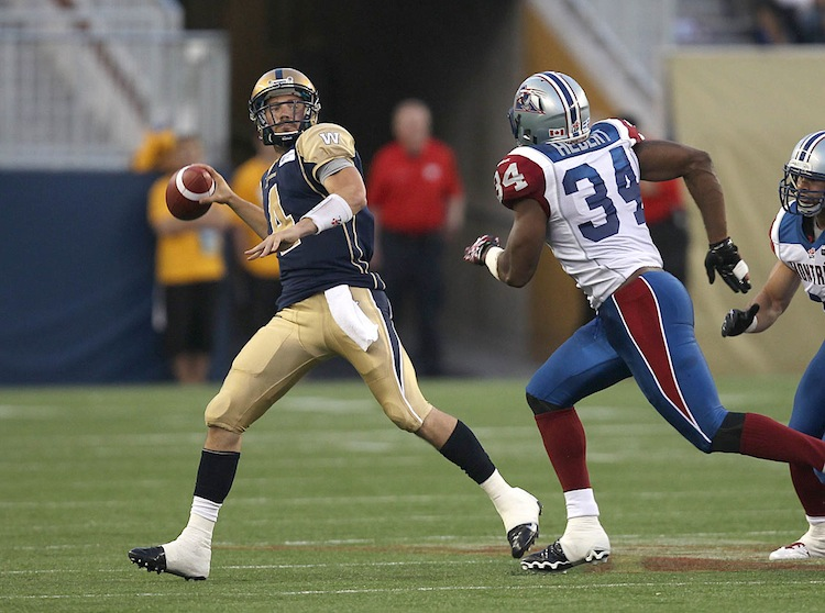 Winnipeg Blue Bombers quarterback Buck Pierce scrambles with the ball as Kyries Hebert of the Montreal Alouettes gives chase during the third quarter.