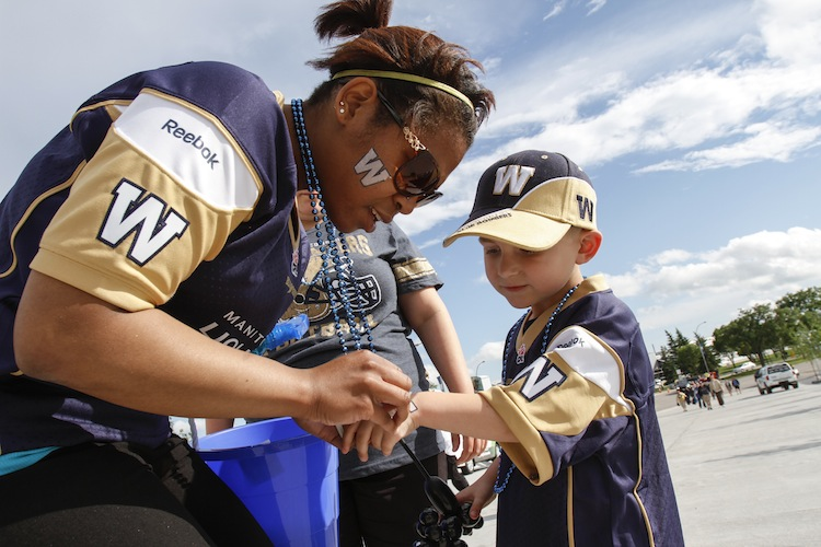 Colby Wieby, 4, gets a temporary tattoo outside Investors Group Field. (JESSICA BURTNICK / WINNIPEG FREE PRESS)