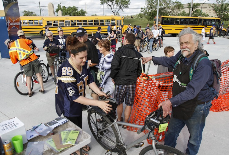 (Right) Bike valet Bill Newman takes care of fans' bikes as Winnipeggers arrive at Investors Group Field. (JESSICA BURTNICK / WINNIPEG FREE PRESS)
