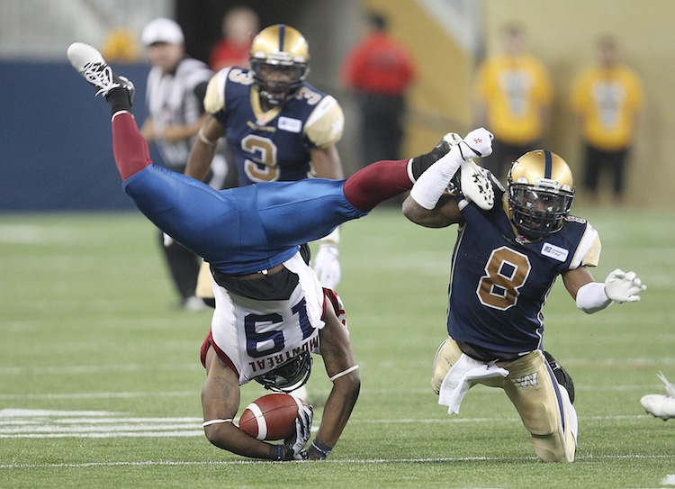 Winnipeg Blue Bombers Brandon Stewart (8) up-ends Montreal Allouettes' S.J. Green (19) during third-quarter action.