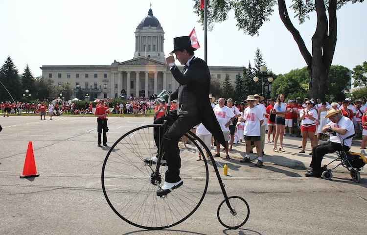 Martin Barnes rides a remake of a 1875 Penny Farthing bicycle during the Living Flag event on teh grounds of the Manitoba legislature. (Mike Deal / Winnipeg Free Press)