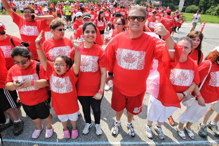 Participants (including Dancing Gabe, giving the thumbs-up) start to take their positions during the Living Flag event. (Mike Deal / Winnipeg Free Press)