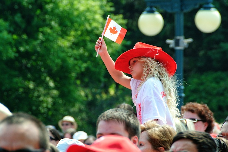 Amber Fitkowski, 6, waves a flag while waiting for the rest of the participants to gather during the Living Flag event on the grounds of the Manitoba legislature. (Mike Deal / Winnipeg Free Press)