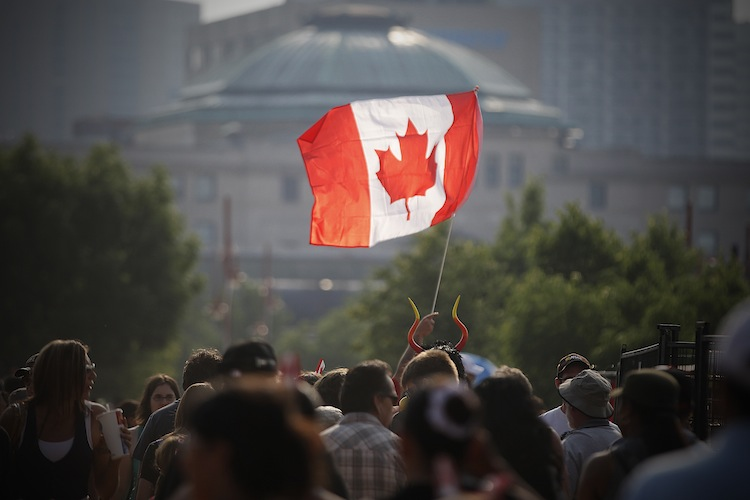 A flag flies high during the Canada Day festivities at The Forks Monday. (John Woods / Winnipeg Free Press)