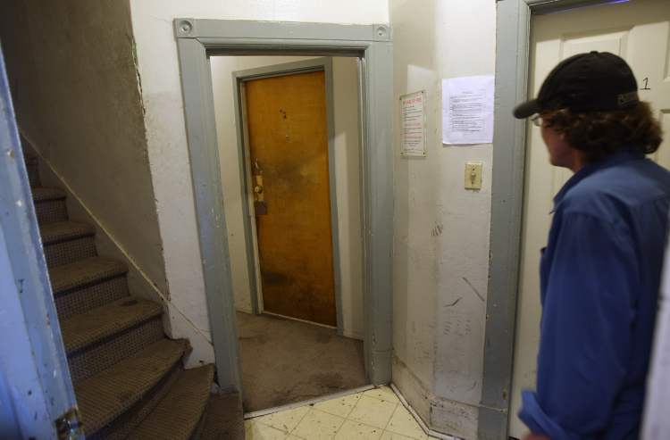 This Spence Street rooming house has 18 suites. Tenant Dave shows the tight hallways in the house.