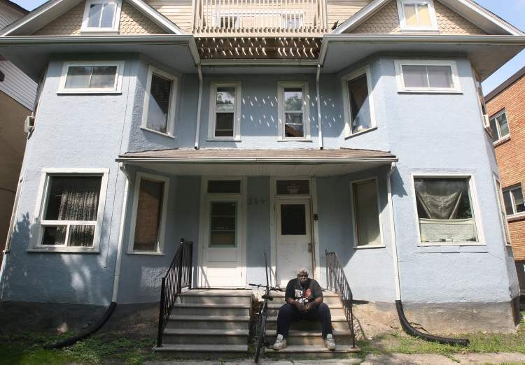 Caretaker Albert believes he needs to sit on porch of the Furby Street rooming house where he works so everyone knows he's around. (JOE BRYKSA / WINNIPEG FREE PRESS)