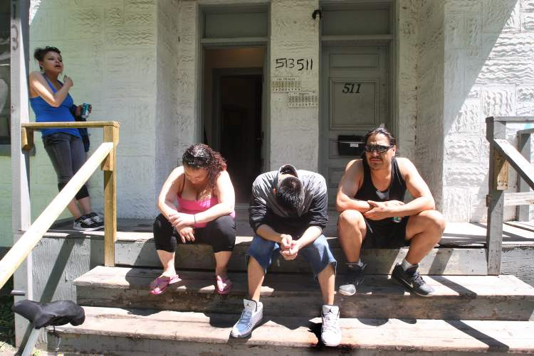 People gather on the front porch of a Spence Street rooming house.  (JOE BRYKSA / WINNIPEG FREE PRESS)