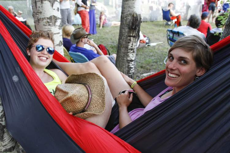 Megan Barrymore (right) and wife Mandolyn share a hammock in a shady nook of the festival grounds. (JESSICA BURTNICK / WINNIPEG FREE PRESS)
