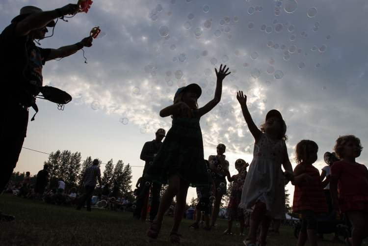 Sisters Avery MacKenzie, 6, and Cadence, 3, try to catch bubbles made by Rich Hamon. (JESSICA BURTNICK / WINNIPEG FREE PRESS)